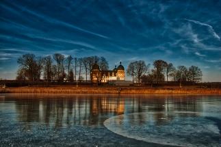 Schloss Seehof und der zugefrorene See im Winter